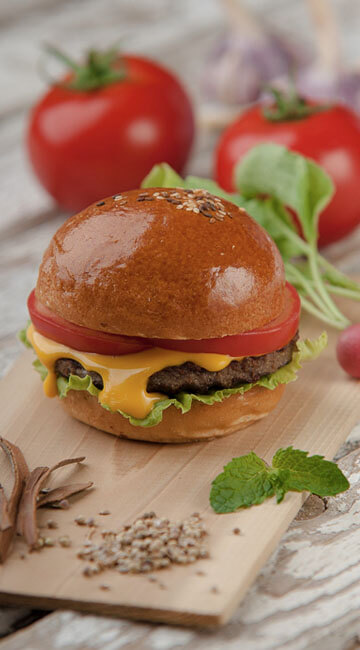 cheeseburger sitting on a cutting board with garnishes